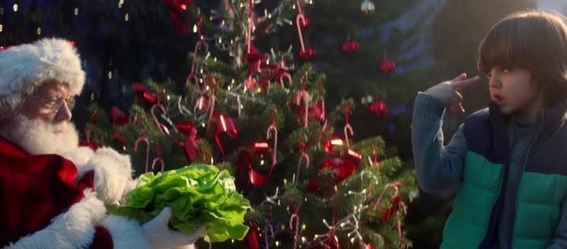 Le Père Noël en train d'accepter une salade pour le spot de Noël d'Intermarché