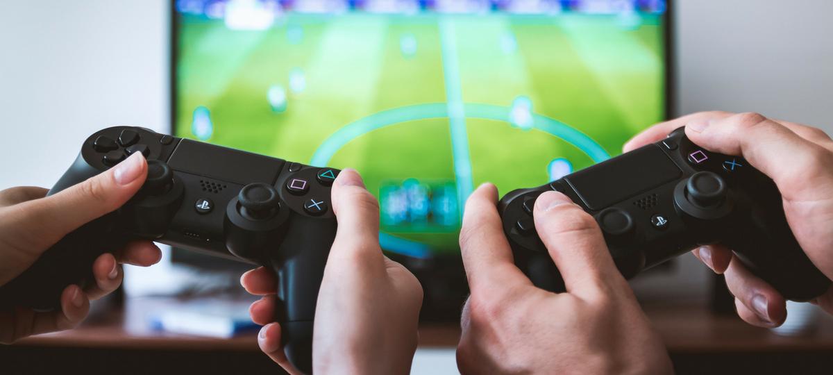Deux manettes de console devant un jeu vidéo de football