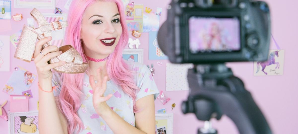 Une influenceuse avec des cheveux roses qui se filme une chaussure à la main