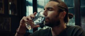 Une homme qui boit de l'eau dans une pinte de Guinness