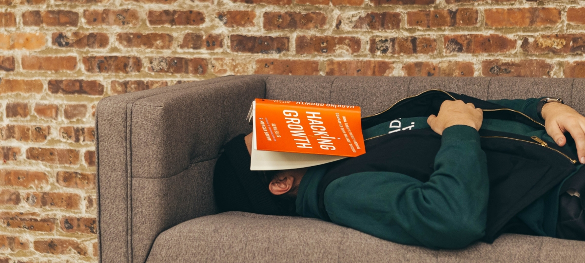 Un homme qui dort sur un canapé avec un livre sur la tête