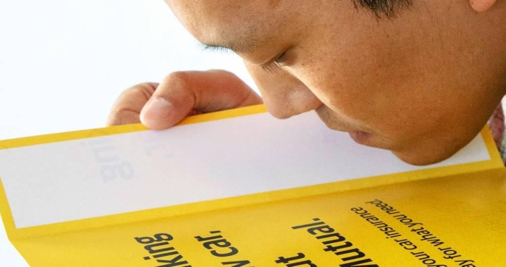 Un homme sent une affiche de écrite noir sur jaune