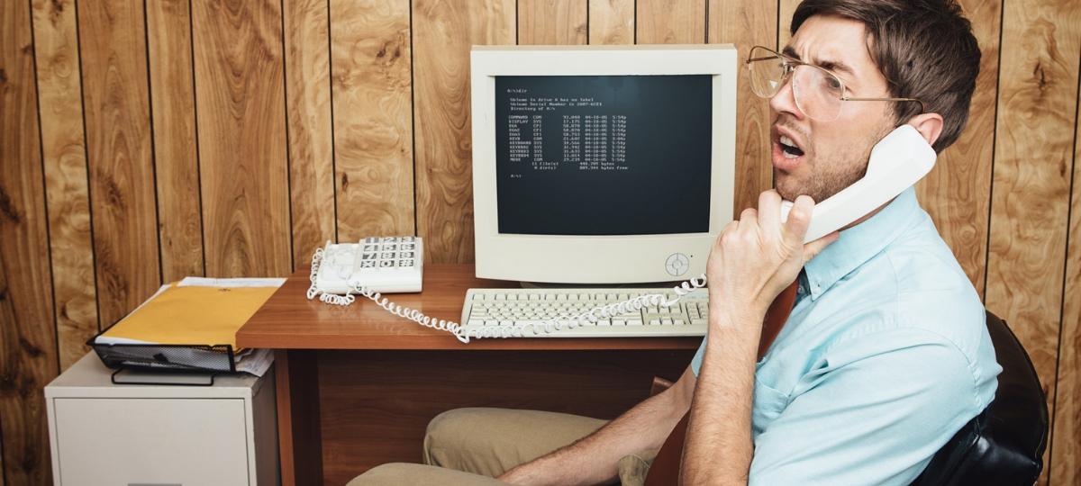 Un homme au travail devant un vieil ordinateur