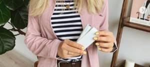 Une jeune femme tient une cigarette électronique IQOS