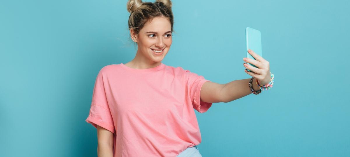 Une femme avec un t-shirt rose qui prend un selfie devant un fond bleu