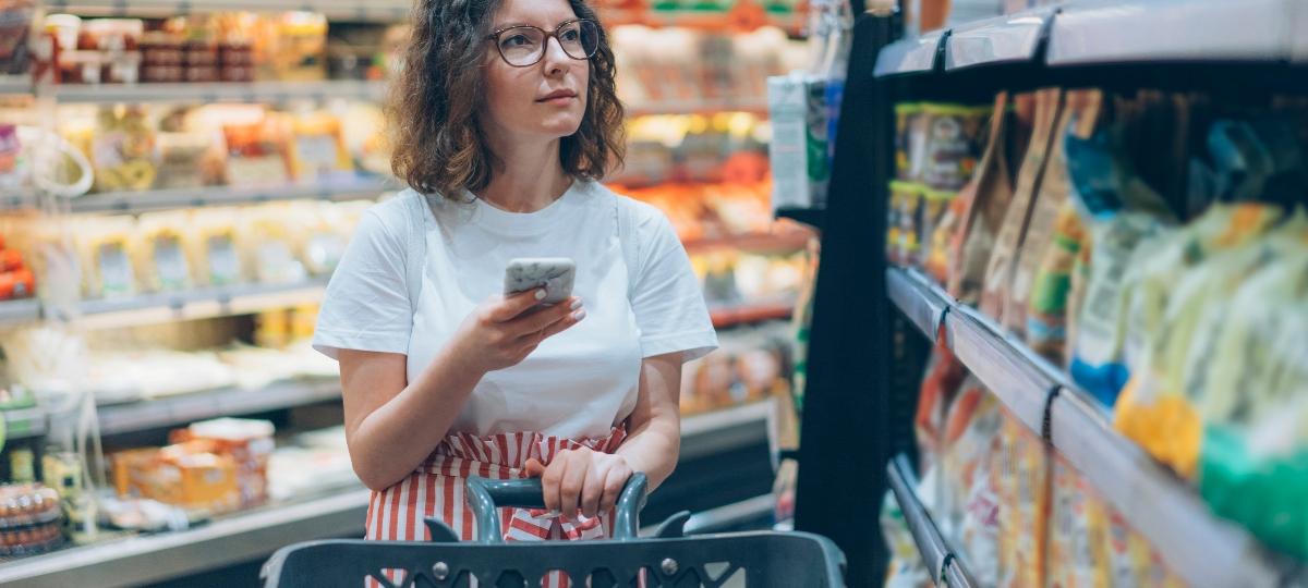 Une femme au supermarché avec son smartphone