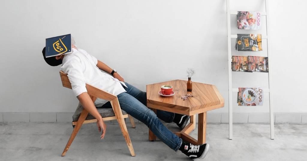 Un homme qui dort avec un magazine sur la tête