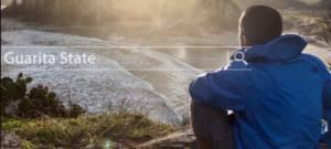 Un homme assis, de dos, dans le nature, porte une veste The North Face