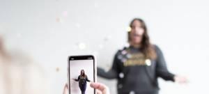 Une jeune femme se fait filmer par son ami, devant un mut blanc