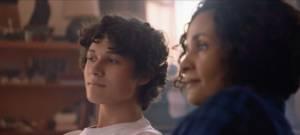 Une mère et son fils regardent la télévision dans leur salon