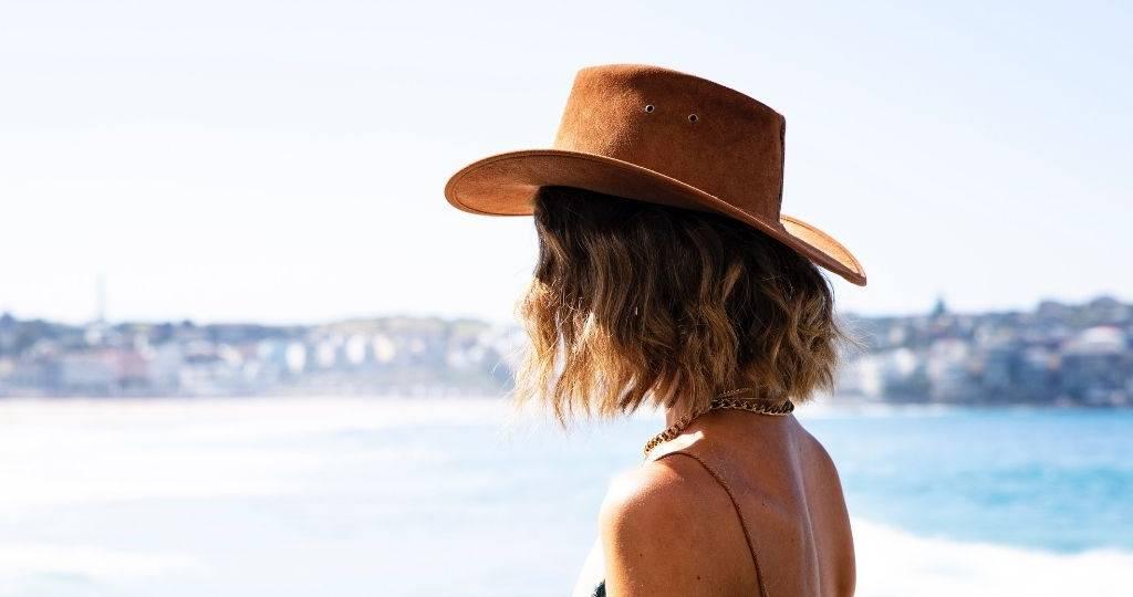Une femme porte un chapeau de dos face à la plage