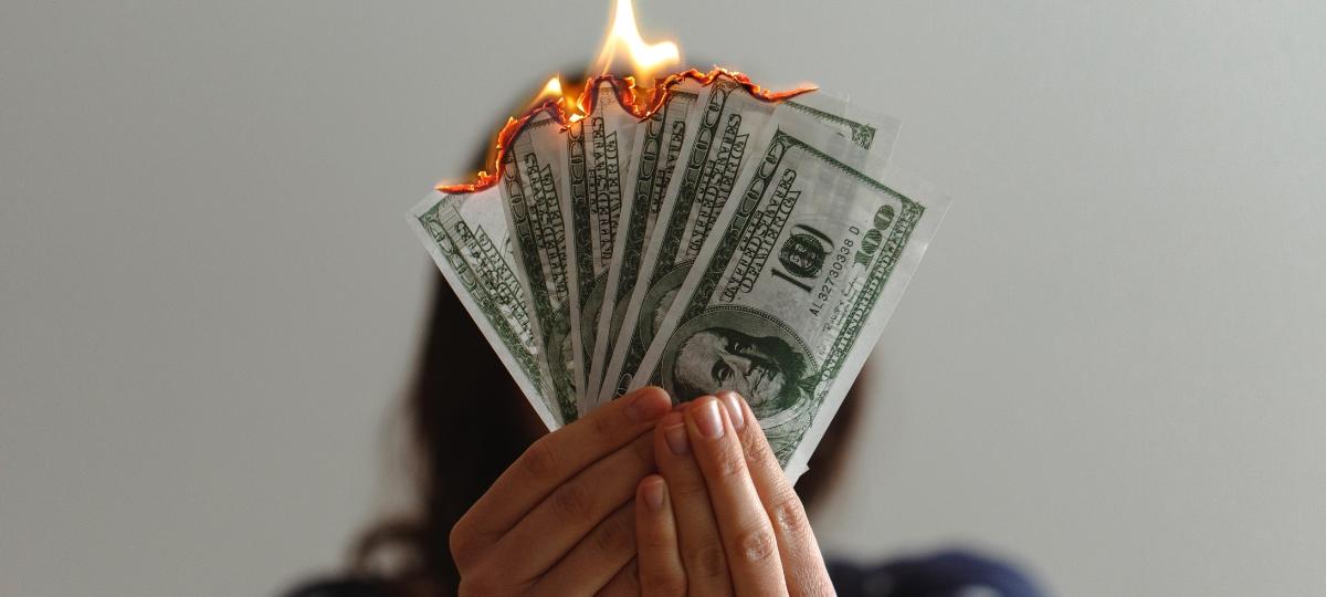 Une femme qui tient des billets de dollars en train de bruler