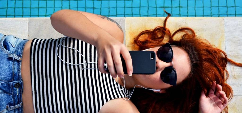 Une fille allongée utilise son smartphone
