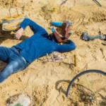 un homme masqué allongé sur le sable