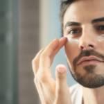 Un homme qui met de la crème sous ses yeux devant un mirroir