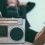 Visuel d'un ancien poste de radio, avec une jeune femme allongée qui a le pied dessus