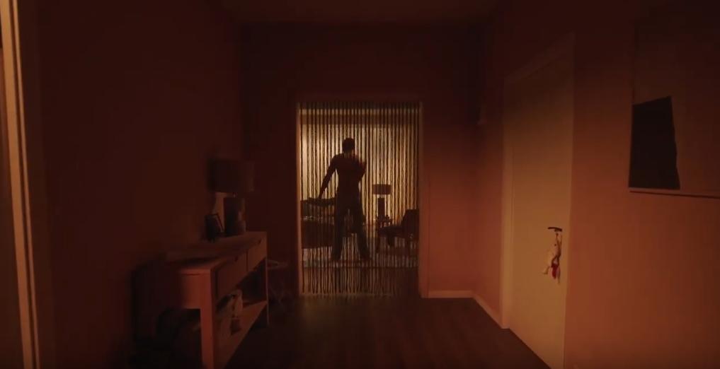 Homme nu de dos au fond d'un couloir, derrière un rideau ajouré