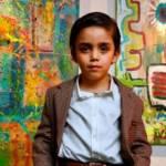 Un enfant artiste pose devant ses peintures