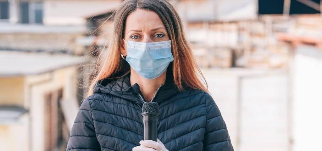 Une journaliste avec un masque et un micro
