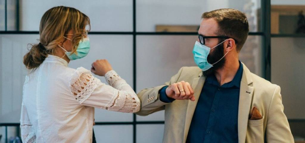 Des gens qui se disent bonjour avec le masque