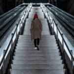 Une femme de dos montant des escaliers
