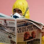 Un homme en combinaison anti-radiations en train de lire un journal