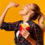 Une jeune femme en train de manger des frites McDonald's