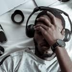 Un jeune homme noir allongé sur son lit entouré d'objets