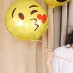 Une femme brune tenant dans la main un ballon en forme de smiley qui envoie un bisou coeur