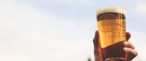 Personne qui lève son verre de bière