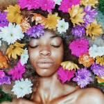 Une femme noire posant sur des feuilles, les cheveux remplis de fleurs