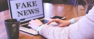 """Jeune femme devant un ordinateur où il y a écrit """"Fake News"""""""