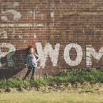 """Petite fille devant un mur de briques rouges sur lequel est inscrit """"Women"""""""
