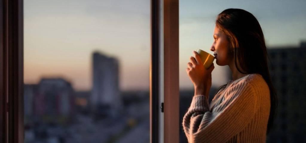 Une femme boit son café à la fenêtre