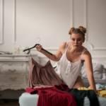 Jeune femme sur son lit avec des vêtements étalés devant elle