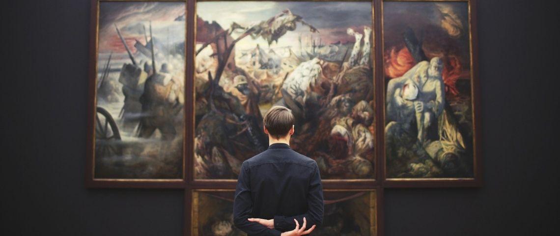 Homme de dos devant un tableau dans un musée