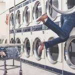 Jeunes femme dans une machine à laver dans une laverie automatique