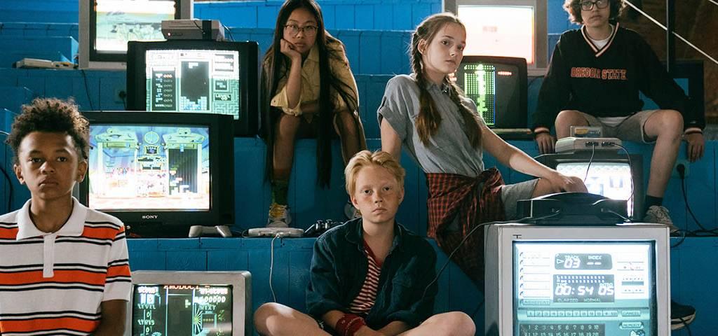 Enfants assis sur des bancs à côté d'écrans