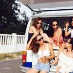 Filles riant assises dans le coffre d'un minibus pr§ès de la plage