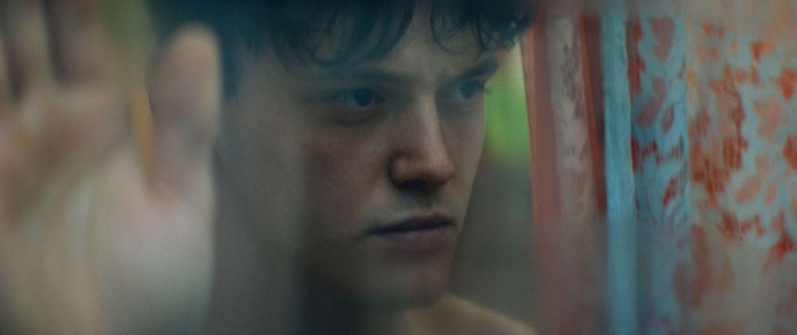 Jeune homme devant un miroir, avec une main tendue pour dire Stop