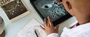 Garcon regardant les cratèresde la lune sur une tablette