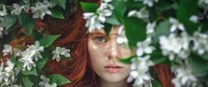 Jeune femme rousse apparaissant dans des feuilles vertes et des fleurs blanches