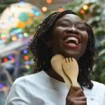 Femme noire avec des couverts à salade en bois, riant aux éclats