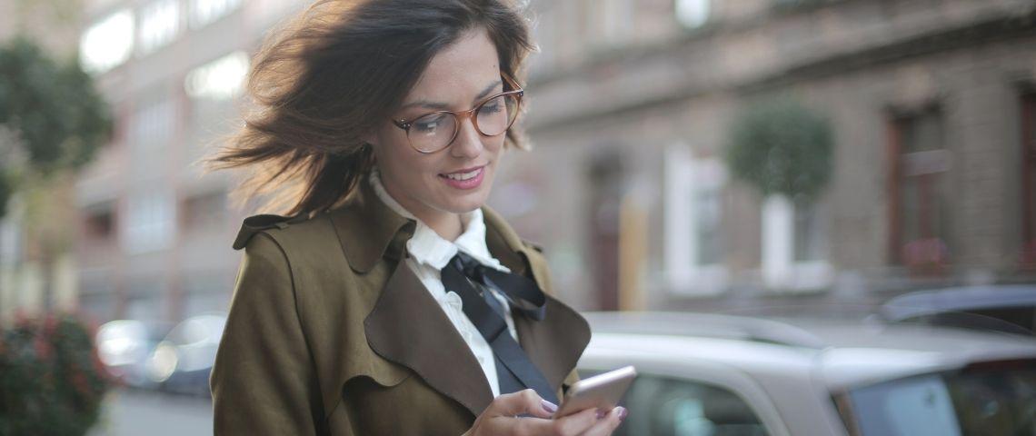 Jeune femme lisant un message sur son portable dans la rue