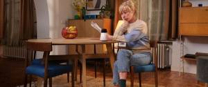 Une femme assise à table, elle a l'air perplexe, elle se pose une question. Nouvelle campagne Axa