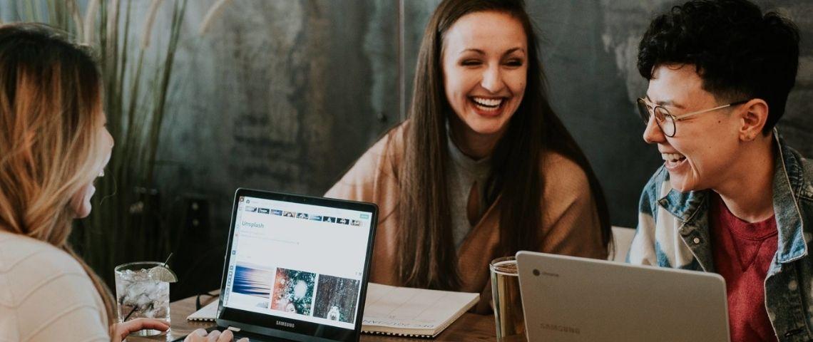 3 jeunes riant devant des ordinateurs