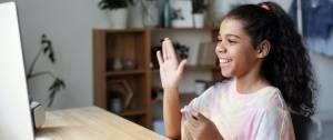 Jeune fille devant son ordianteur, levant la main pour dire bonjour à son enseignant en ligne