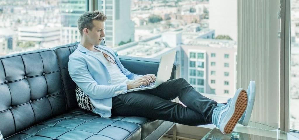 Un homme écrit sur un ordinateur
