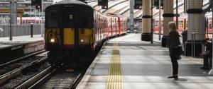 Un train qui arrive dans sa voie, une femme attend