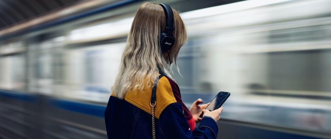 Une femme qui écoute du son au travers d'un casque de musique. Elle se trouve dans une station de métro